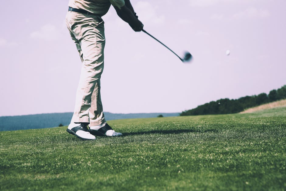 A person in a green field with a golf club